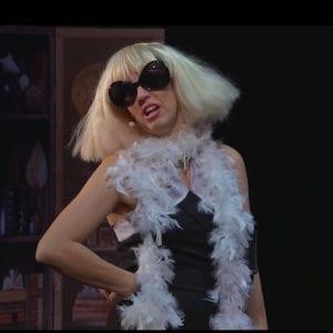 Photo du spectacle : une jeune fille blonde avec lunettes de soleil, la main sur la hanche, fait tourner ses cheveux.