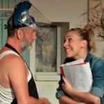 une homme avec un masque de soudaeur ouvert face à une jeune femme souriante