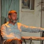un homme assis devant le mur d'une petite maison