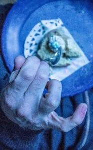 Un main vue de dessus tenant une cuillère, petit doigt levé