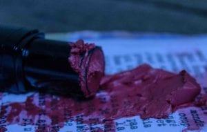 un tube de rouge à lèvre écrasé sur un texte imprimé