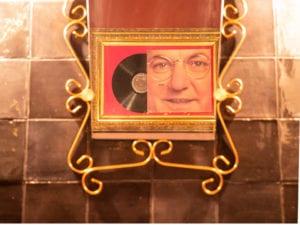 détail du couloir : photo de coluche et de son disque