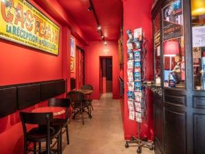 Couloir vers la salle de spectacle avec le guichet à droite, de petites tables à droite. Au fond l'entrée des toilettes.