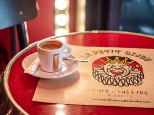 """Détail d'une table avec un café et un set de table au couleurs du bar """"Le Petit Bijou Café Théâtre"""" à Biarritz ."""