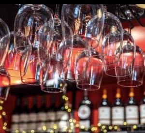 Détail du bar, avec les verres de vins accrochés au dessus du comptoir