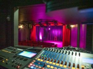 La scène du Petit Bijou vue depuis la cabine de régie. Premier plan technique et mélange de rouges et de violets sur la scène
