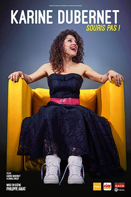 Affiche du spectacle Karine Dubernet assise sur un fauteuil, très souriante, dans souris Pas !