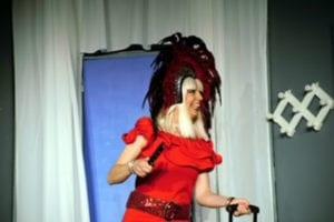 """Photo de """"Demain je me marie"""" une femme debout avec robe rouge et haute coiffe noire"""