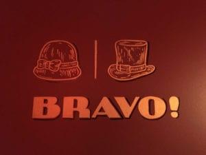 Entrée des toilettes au bout du couloir avec le mot bravo, et des chapeau, l'un de femme, l'autre d'homme