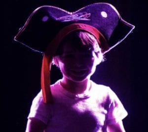enfant en contre jour dans un atelier et en costume de pirate