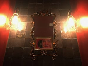Miroir des toilettes des années 50 avec le reflet de Coluche