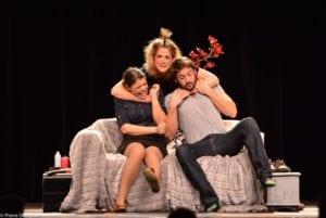 un homme une femme sur un canapé et une autre femme derriere qui les enlace par le cou un peu trop fort
