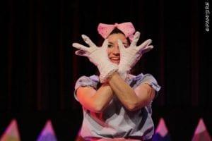 Alouette avec un noeud rose sur la tête, les bars croisés, mains vers le haut avec les doigts écartés
