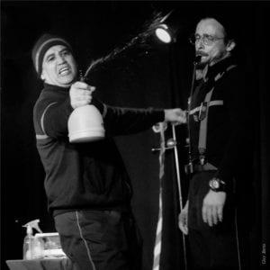 photo noir et blanc de deux pompiers qui arrosent la scène