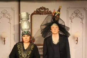 deux femmes avec des chapeaux étranges : une urne et une bouteille magnum..
